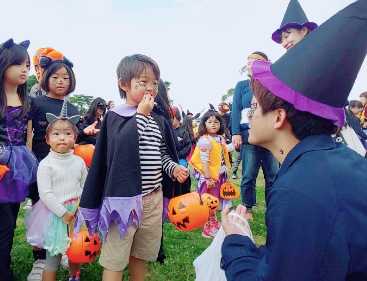 TETTE会のハロウィンパーティーにて学生が子供にお菓子をあげている写真